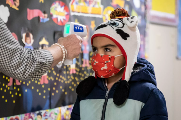 A preschool student gets his temperature checked this morning as he walks into Dawes Elementary School at 3810 W. 81st Pl. on the Southwest Side. | Ashlee Rezin Garcia/Sun-Times