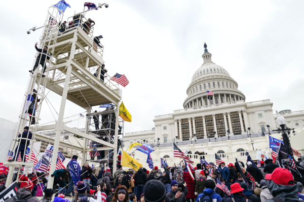 Supporters loyal to President Donald Trump clash with authorities before successfully breaching the Capitol building. | John Minchillo/AP Photo