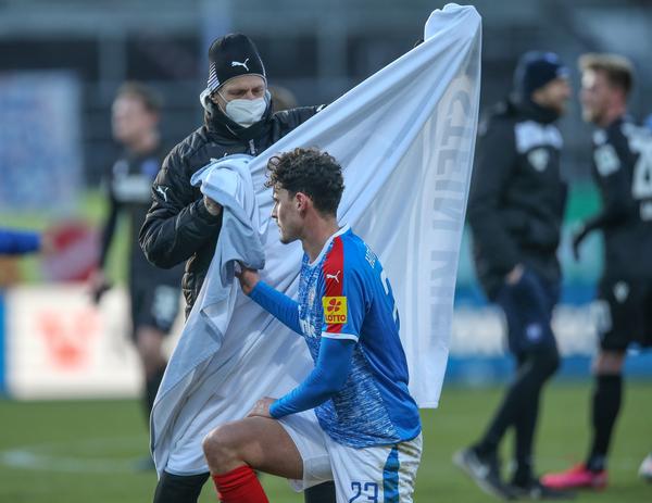Teamarzt Dr. Martin Mrugalla bietet Janni Serra nach dem 2:3 gegen den Karlsruher SC eine Decke an. Der Stürmer hüllt sich nach dem ihm untersagten Winter-Wechsel in den Mantel des Schweigens. Foto: Uwe Paesler