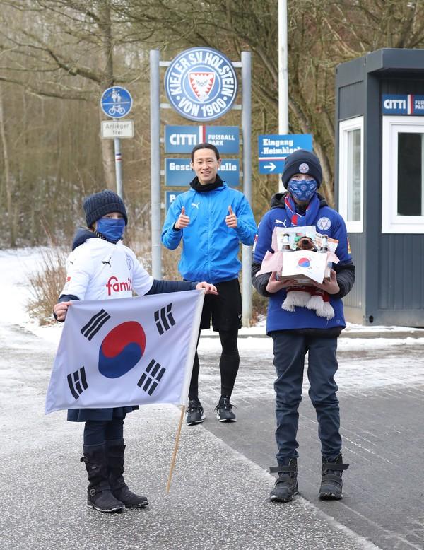 Prost Neujahr! Für Holsteins Südkoreaner Jae-Sung Lee (hinten) und viele andere Asiaten beginnt erst heute das neue Jahr. Als Überraschung brachten zwei Holstein-Fans gestern Geschenke zum Trainingsplatz. Foto: Patrick Nawe