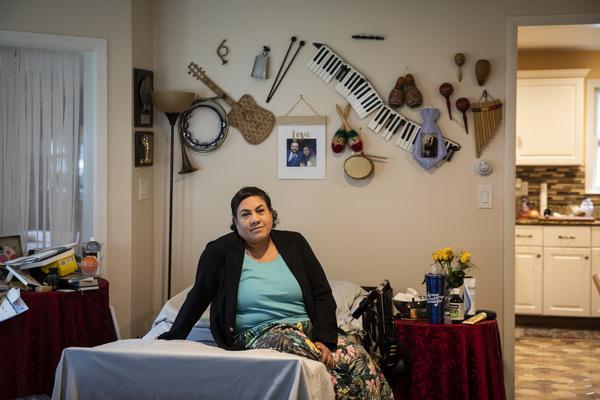 Karla Taylor-Bauman, 50, sits on her adjustable hospital-type bed in the living room of her parents' North Chicago home. | Ashlee Rezin Garcia/Sun-Times