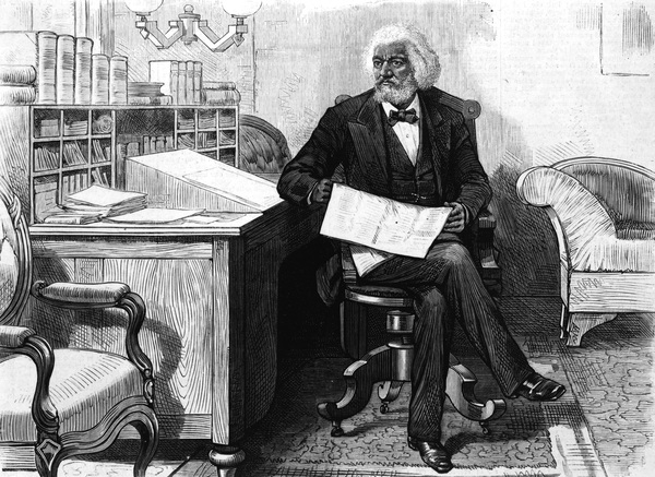 American orator, editor, author, abolitionist and former slave Frederick Douglass (1818-1895) edits a journal at his desk, late 1870s. Photo by Hulton Archive/Getty Images
