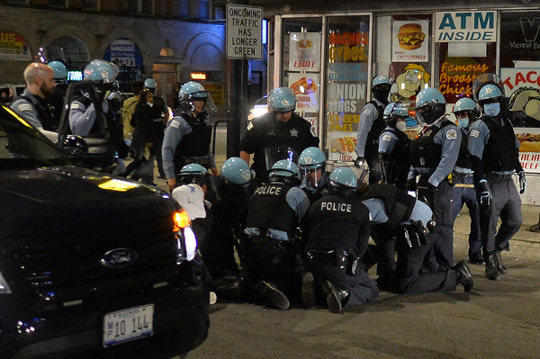 At least 7 police officers involved in detaining a woman near the intersection of Montrose, Broadway, and Sheridan on the North side of Chicago as looting and violence spread later that night on Monday, June 1, 2020.  | Victor Hilitski/For the Sun-Times
