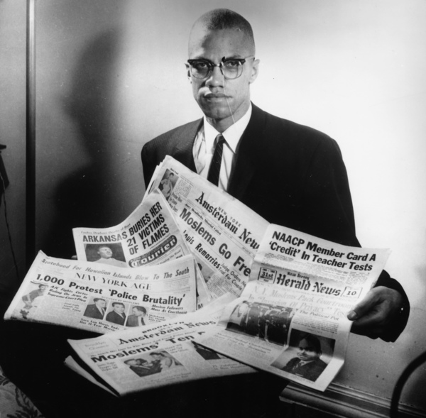 Portrait of human rights activist Malcolm X reading stories about himself in a pile of newspapers, circa 1963. | Photo by Three Lions/Hulton Archive/Getty Images