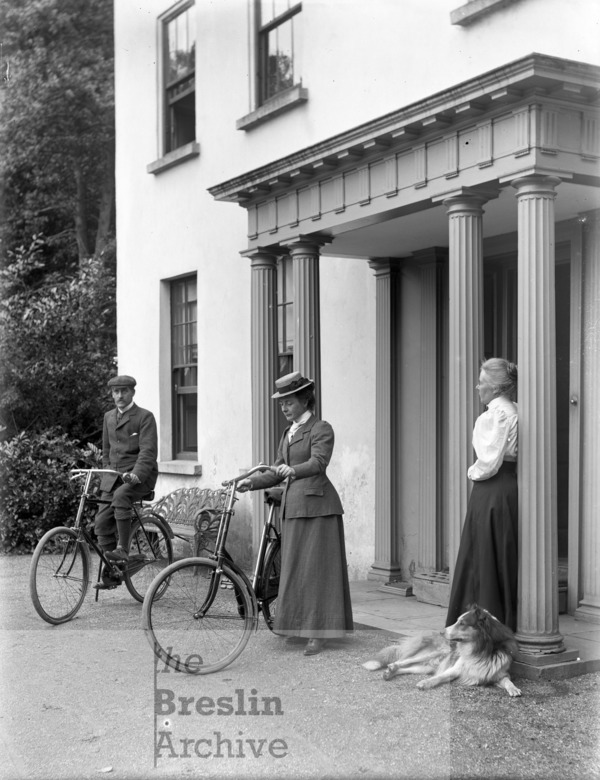 Man and woman with bicycles, Ellie Russel and dog, in front of Brook Lodge, County Waterford.