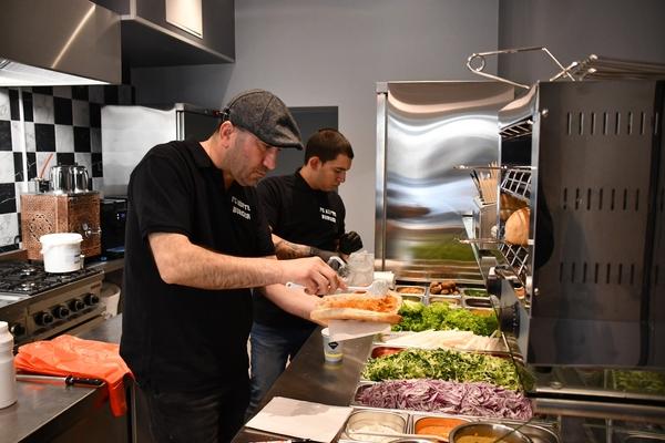 Fikret Arslan (l.) und Konstantin Borisov bereiten Köfte im Brot zu. (Foto: Großmann)