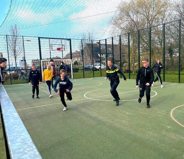 Politieagenten voetballen met jeugd