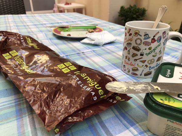 Primer plano de tazas, platos y otros enseres de mi desayuno de hoy en el patio, con cierto product placement no remunerado.