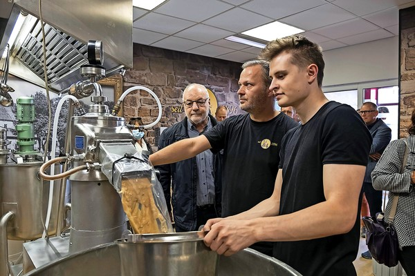 Patrick Lange (vorne) zeigt, wie die Senfherstellung funktioniert. Foto: Jens Wegner