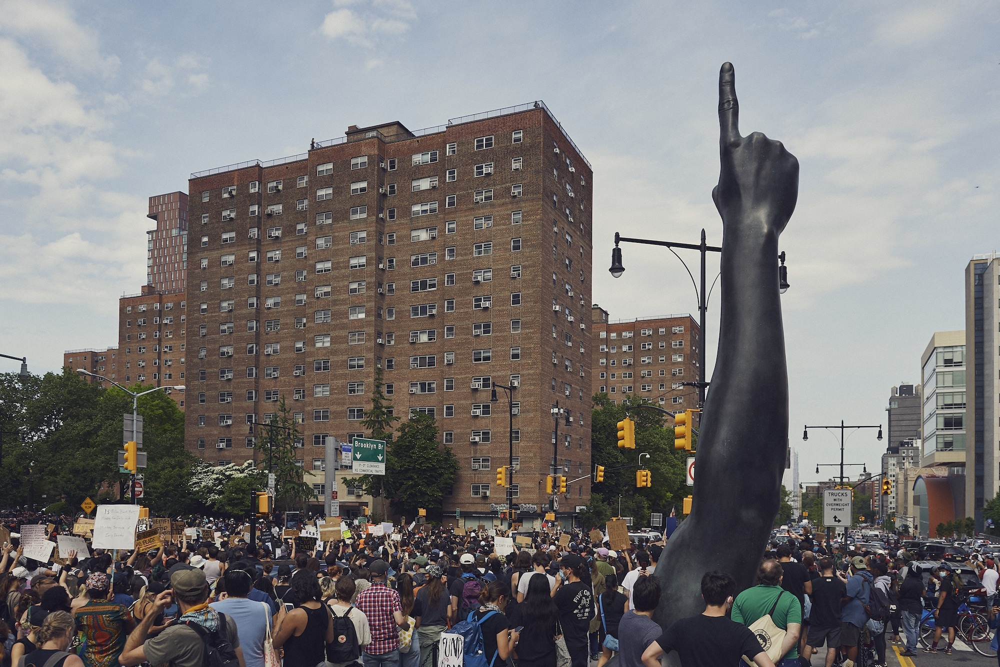 """Attendees of the George Floyd Memorial march near Hank Willis Thomas's """"Unity"""" sculpture, June 2020. (by Jon Vachon, courtesy Center for Brooklyn History)"""