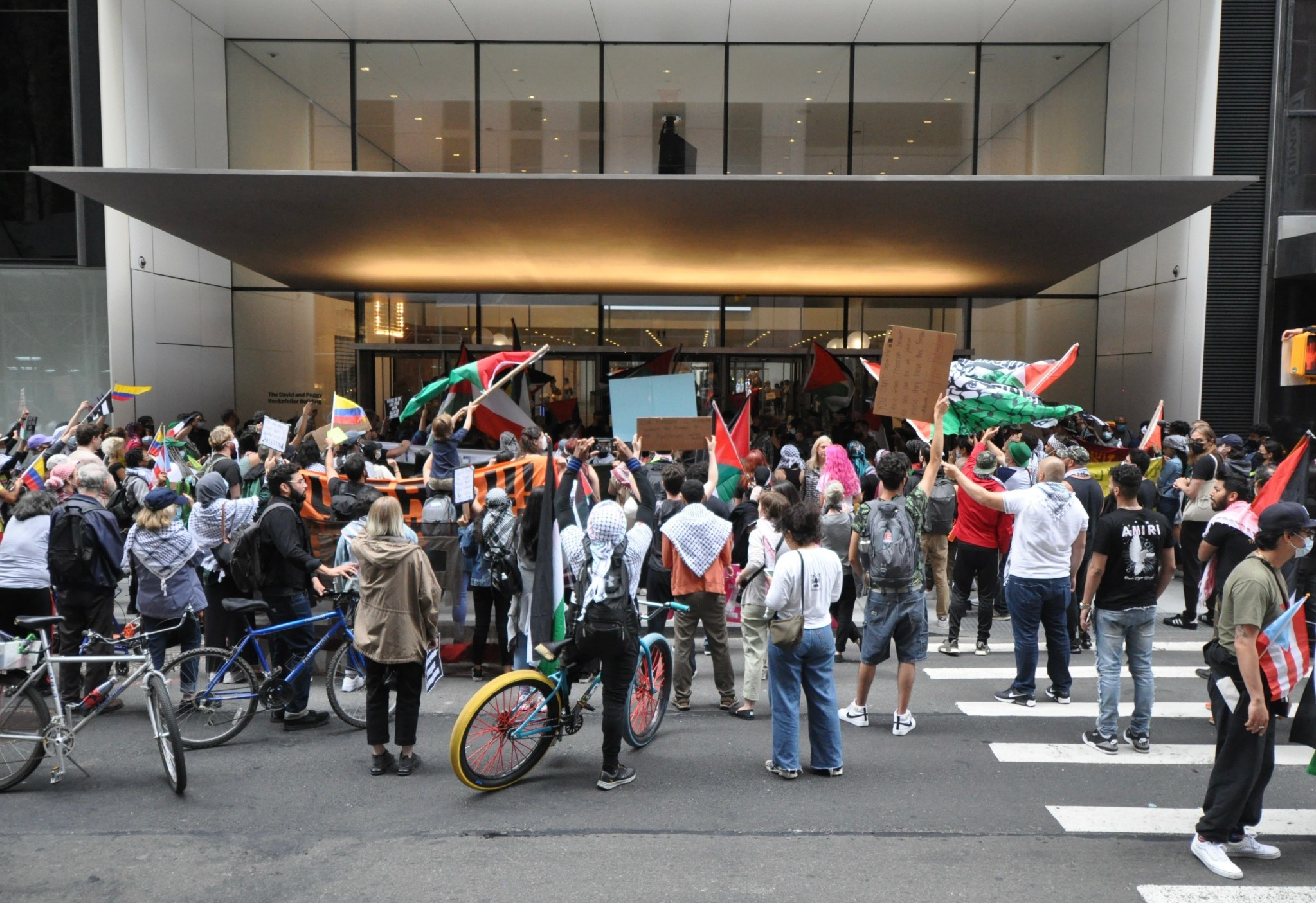 """""""Strike MoMA"""" protesters crowded around the museum entrance and waved flags."""