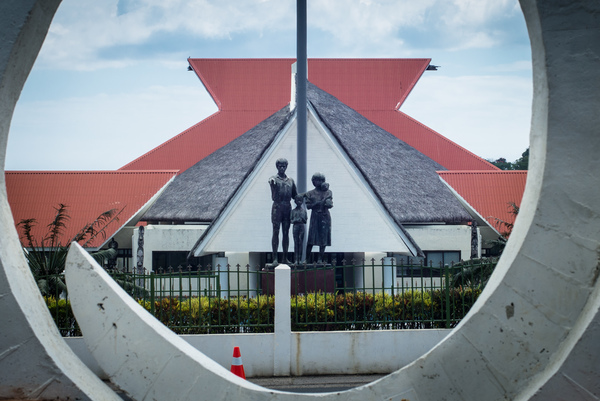 Parliament House in Port Vila, seen through a pig tusk statue across the road.