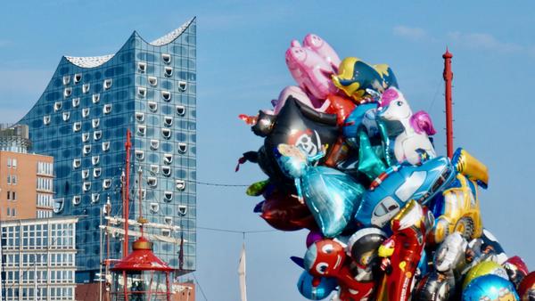 Sur les quais de l'Elbe, un vendeur de ballons et l'Elbphilharmonie en arrière-plan (AD)