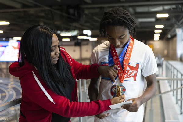"""LaToya Pitner adjusts her son Treyshun Green's medals after the """"Fastest Kids in Chicago"""" final at the Gately Park Indoor Track and Field. 
