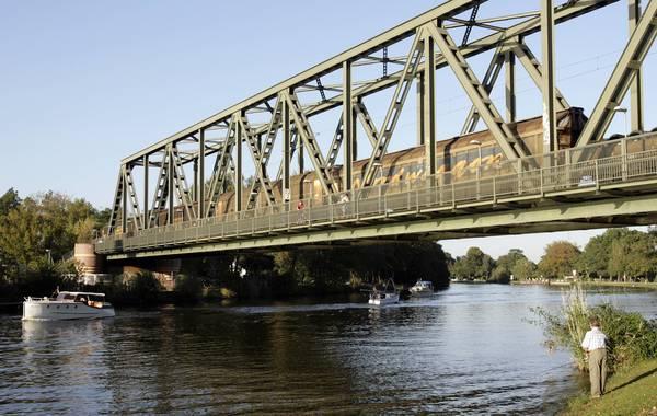 Die Eisenbahnbrücke bietet auch einen Fußweg, auf dem wir das Wasser überqueren. Foto: imago/Enters