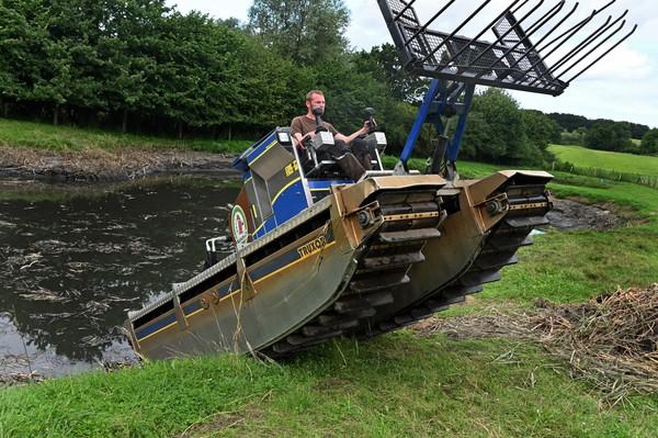 Mit Amphibienfahrzeugen werden in Malente Gewässer gereinigt.