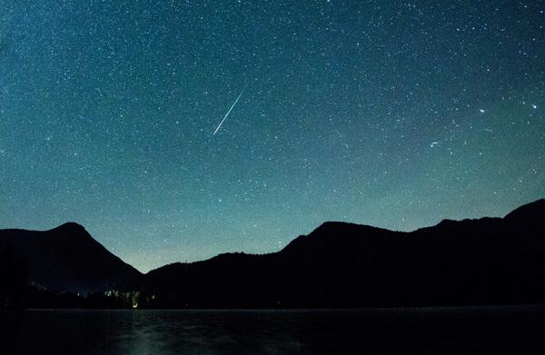 Eine Sternschnuppe leuchtet neben der Milchstraße am Himmel. (Foto: dpa)