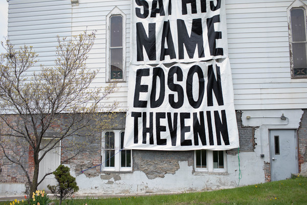 A banner on Oakwood Community Center, April 17 2021. Say his name: Edson Thevenin.