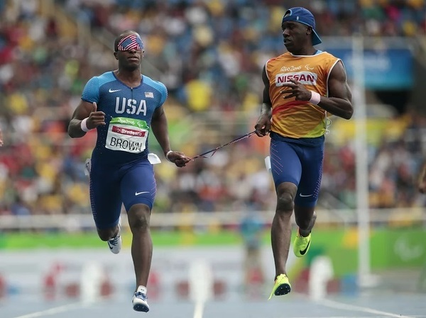 David Brown (left) runs the men's 100 meter T11 round 1 on day 3 of the Rio 2016 Paralympic Games on September 10, 2016 in Rio de Janeiro, Brazil. He is competing in Tokyo with a new partner, Moray Steward. Alexandre Loureiro/Getty Images