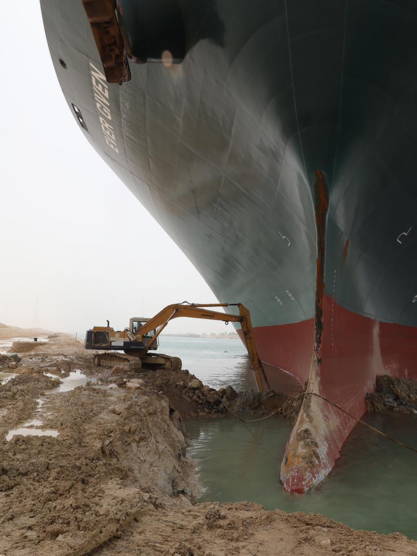 Lone excavator trying to refloat a giant cargo ship