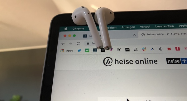 AirPods baumeln am MacBook Display