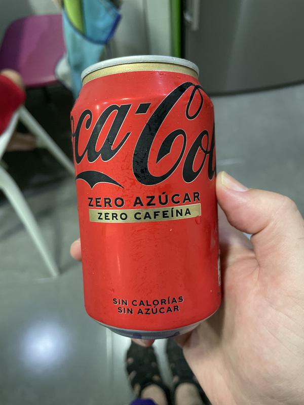Foto del nuevo diseño, sin la doble banda arriba, y con las letras de Coca-Cola en negro.