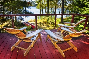 adirondack chairs on deck by lake