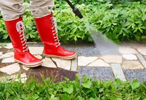 Person in galoshes power washing a walkway