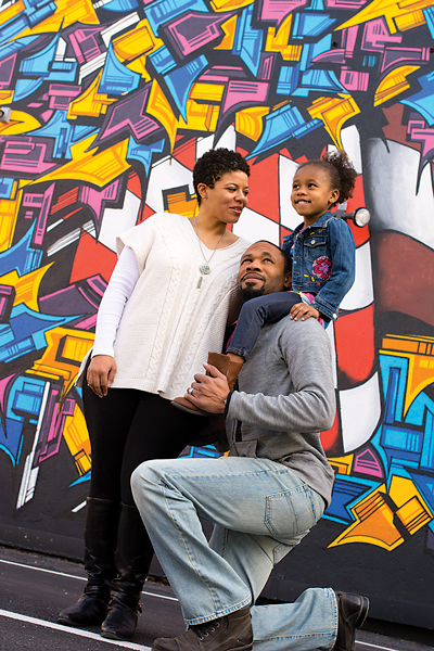 Taekia Glass is program director at ART 180, across the street from this mural. Taekia and Hamilton's daughter, Sanaa, is riding high on Daddy's shoulders.
