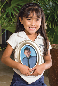 Abril holds a photo of her oldest brother, Julio Cesar, who wasn't available for the family picture on the previous page.