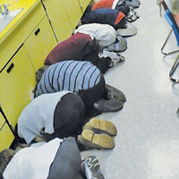 Students demonstrate proper technique during a statewide tornado drill.