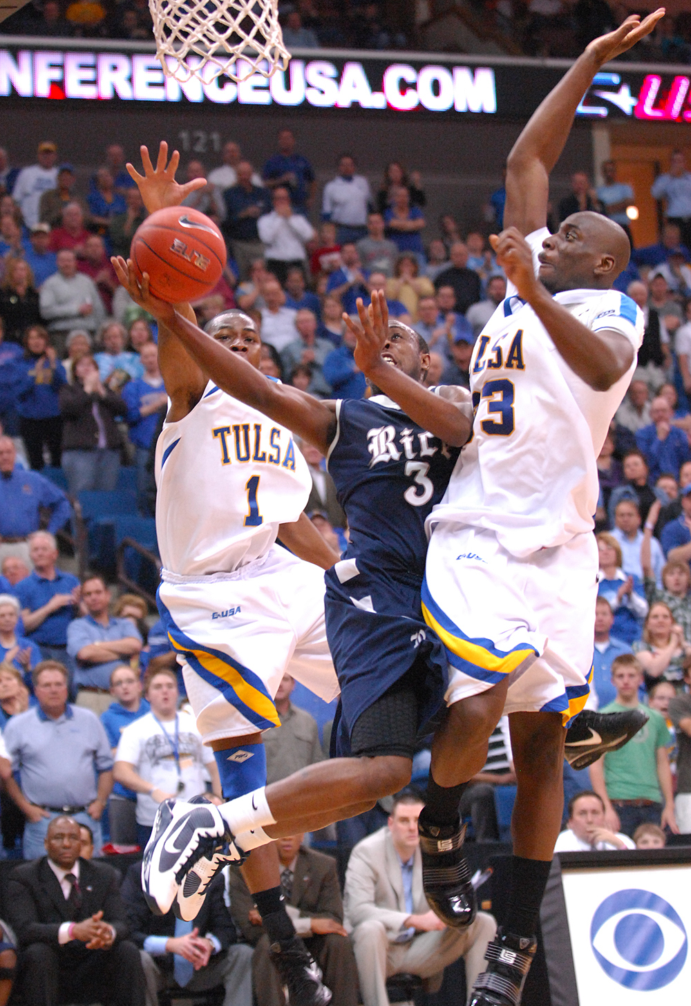 Rice freshman Tamir Jackson draws contact from both Ben Uzoh and Joe Richard during first-round action of the GMC Sierra Conference USA Championship.