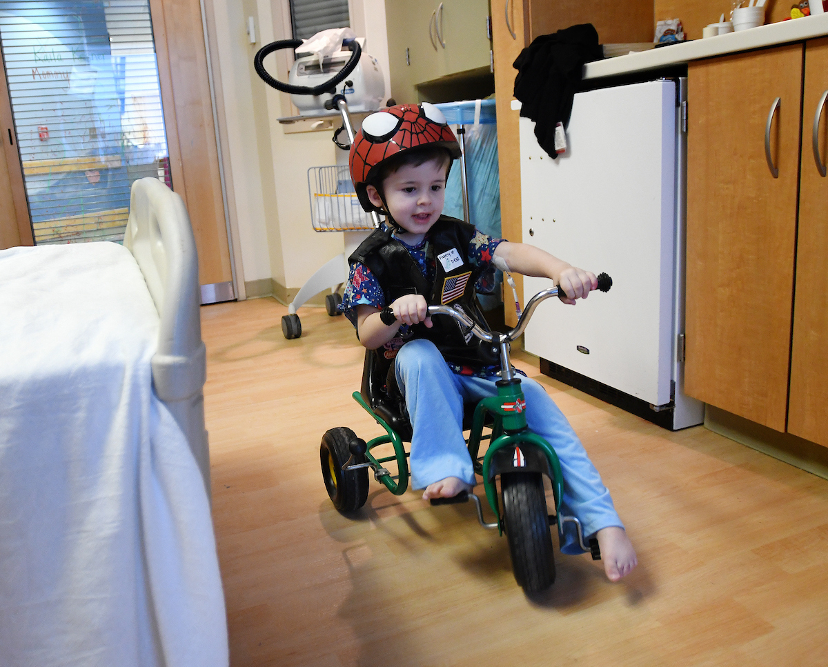 Deacan riding a bike in hospital room