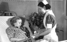 "A nurse bandages a girl's arm at Riley in this undated photo. Providing ""scrap books"" was important to Porter. Credit: IUPUI University Library Special Collections and Archives"