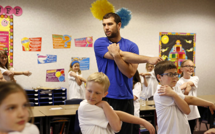Luck leads third-grade class in a warm-up activity during surprise class visit.