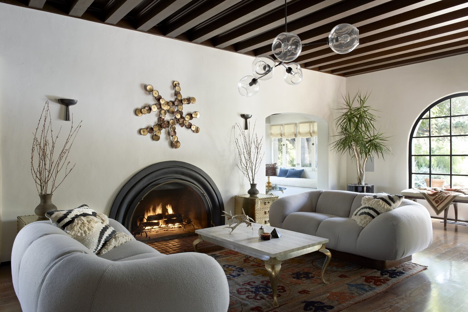 living room with fire place and gray sofa designed by Tamara Honey