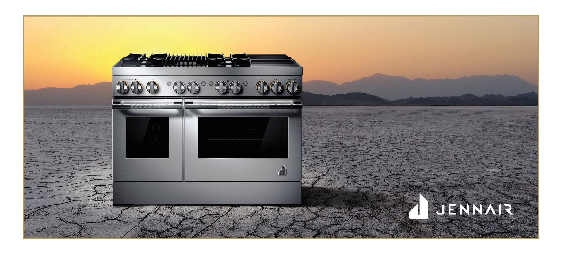 JennAir Rise Dual-Fuel Professional-Style Range in silver with brass accents. Range is in the desert with a beautiful sunset behind.