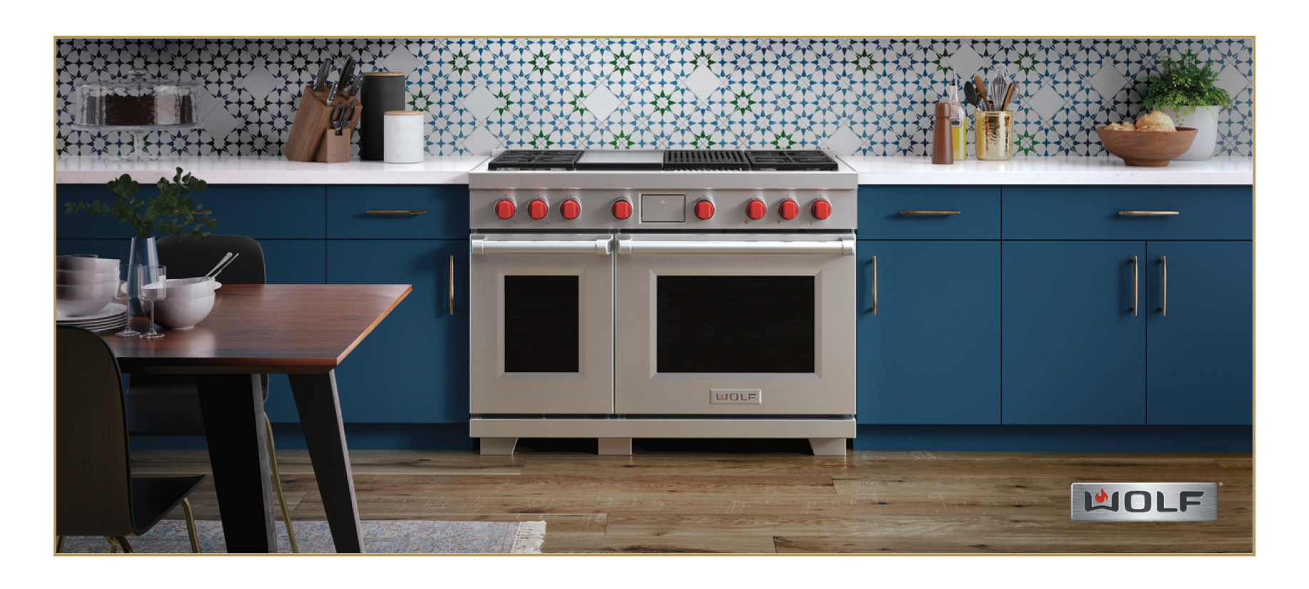 Wolf Dual Fuel Range in silver with red knobs. In the center of a blue kitchen.