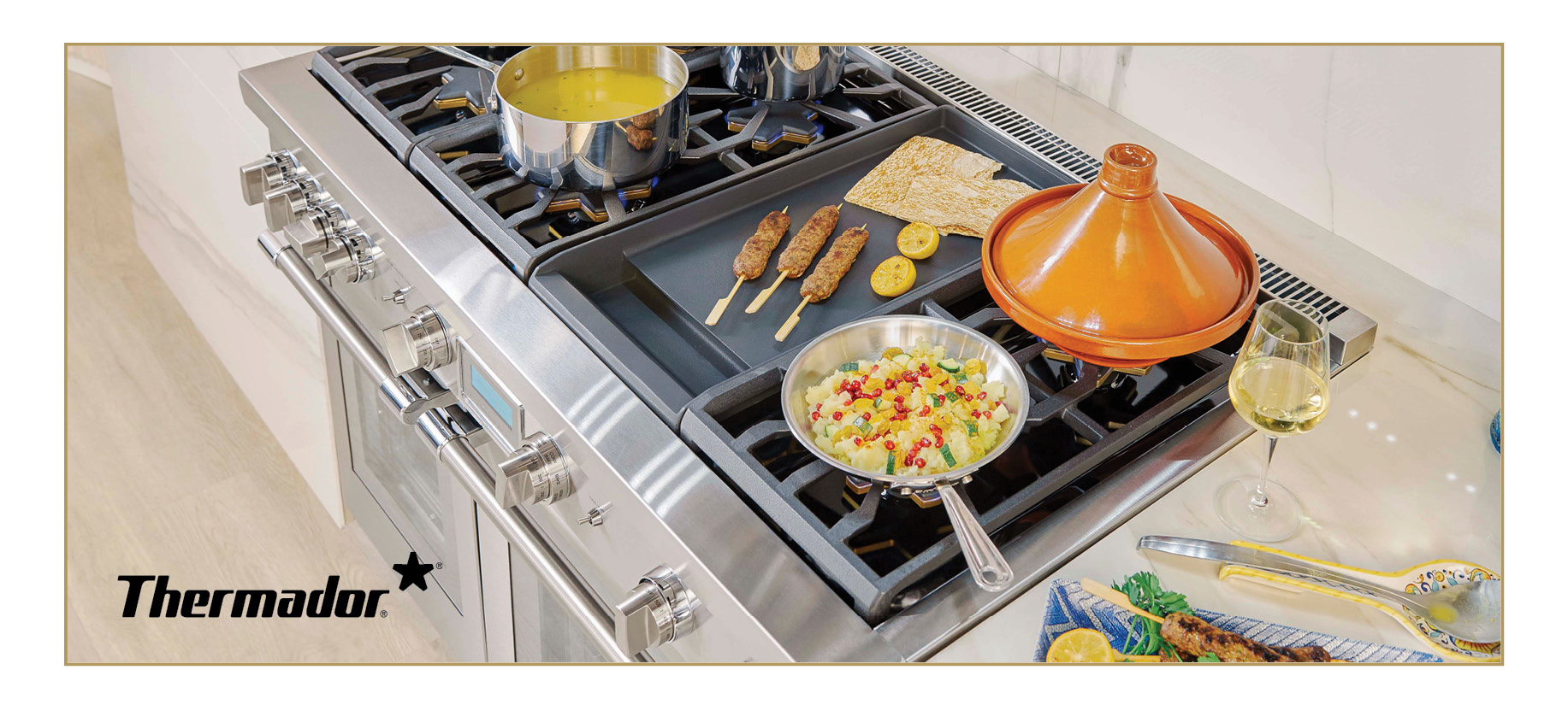 Thermador Dual Fuel Professional Range in silver. Pots and pans with food are arranged on top of the range. A glass of wine is placed to the side.