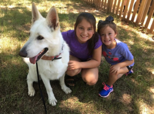 2 girls sitting next to White German Shepherd