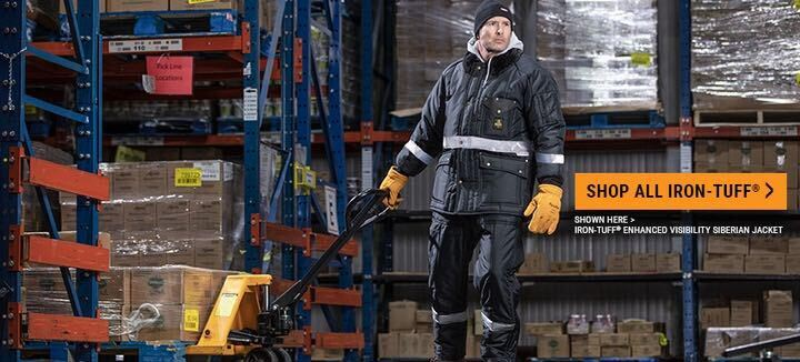 Man wearing freezer jacket, insulated gear with pallet jack in freezer warehouse. Button to shop Iron-Tuff Collection