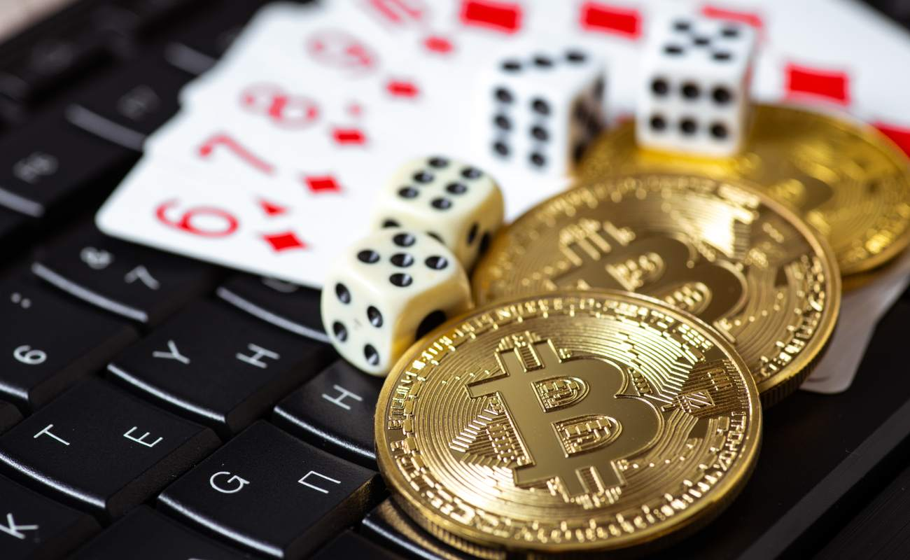 Bitcoins, cards and dice on keyboard.