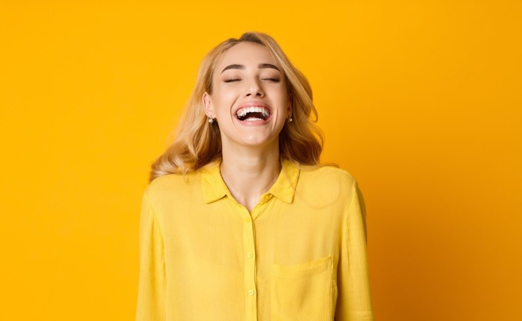 Woman laughing out loud standing against yellow background while wearing a yellow top