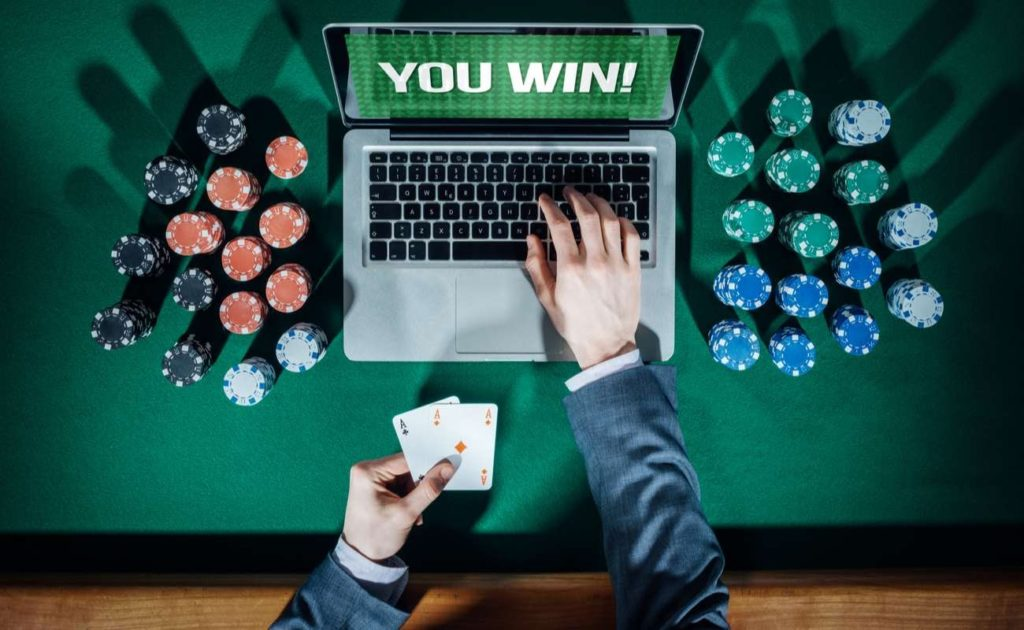 Top view of online player's hands holding cards with laptop and stack of chips on green table
