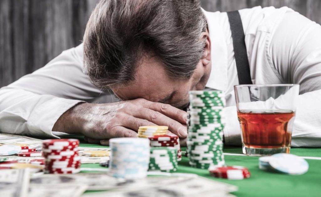 Depressed man leaning his head at poker table with money and gambling chips surrounding during poker loss