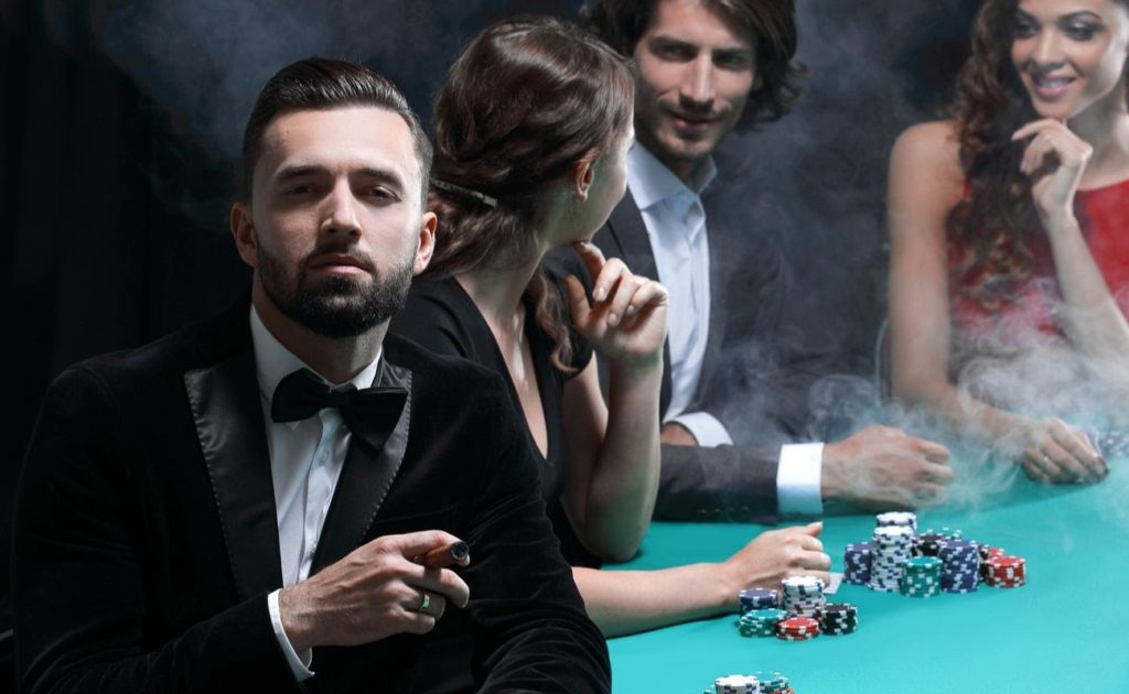 Man in tuxedo with cigar looking up from poker table in casino