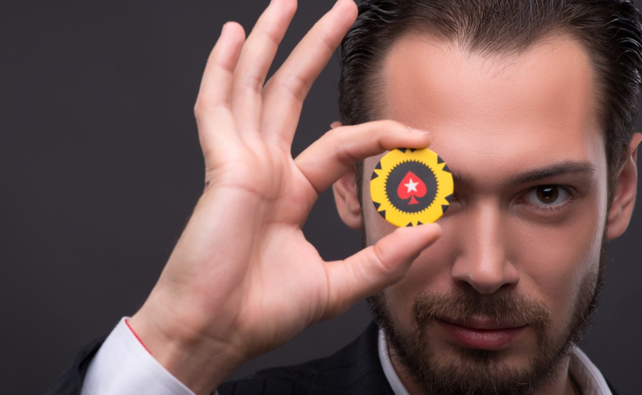 A man showing an ok sign with one yellow chip