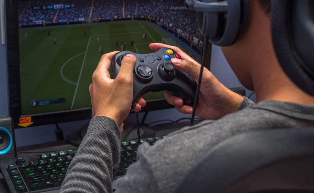 Back view of gamer holding a controller while playing a video game