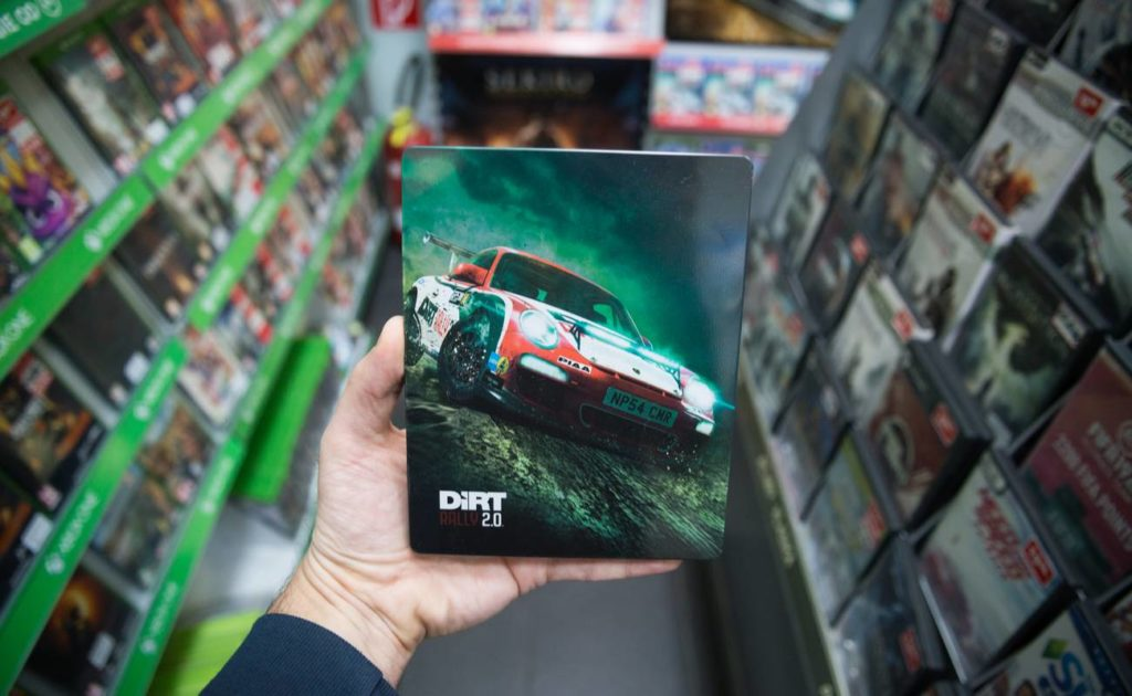 Man holding Dirt Rally 2.0 videogame on Sony Playstation 4 console in store