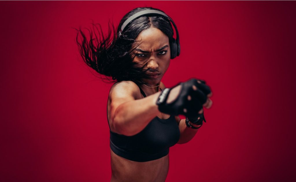 female boxer practicing boxing against a red background